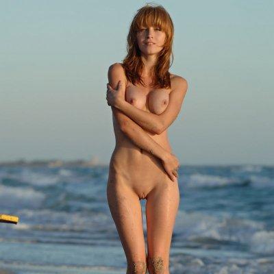 Skinny redhead girl walking naked on the beach